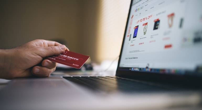 Someone holding a bank card ready to make a purchase online.